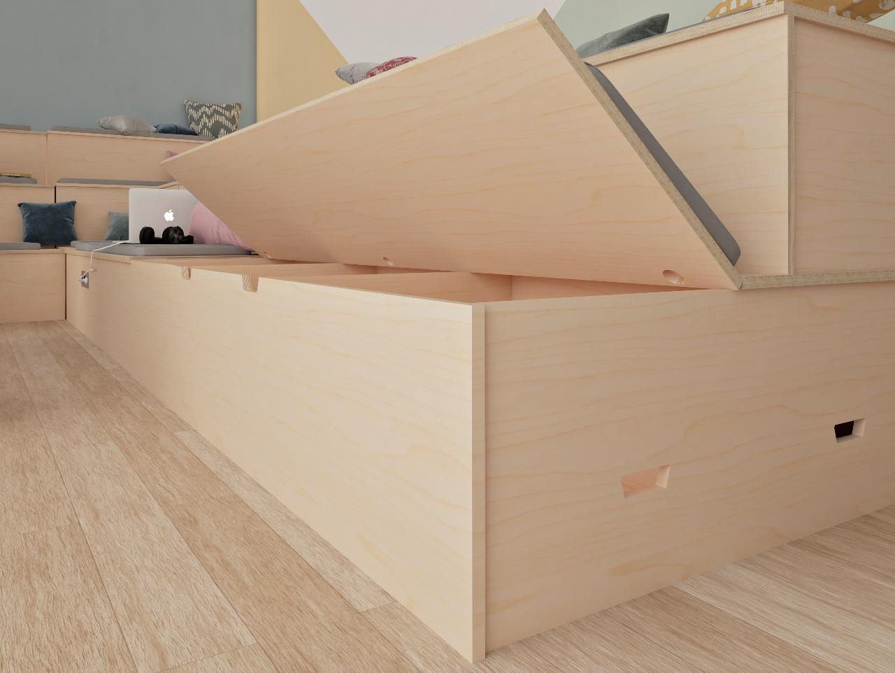 Coffre de rangement qui s'ouvre dans une banquette en bois sur 3 niveaux décorée de plusieurs coussins colorés et accessoirisée de prises électriques pour brancher les ordinateurs