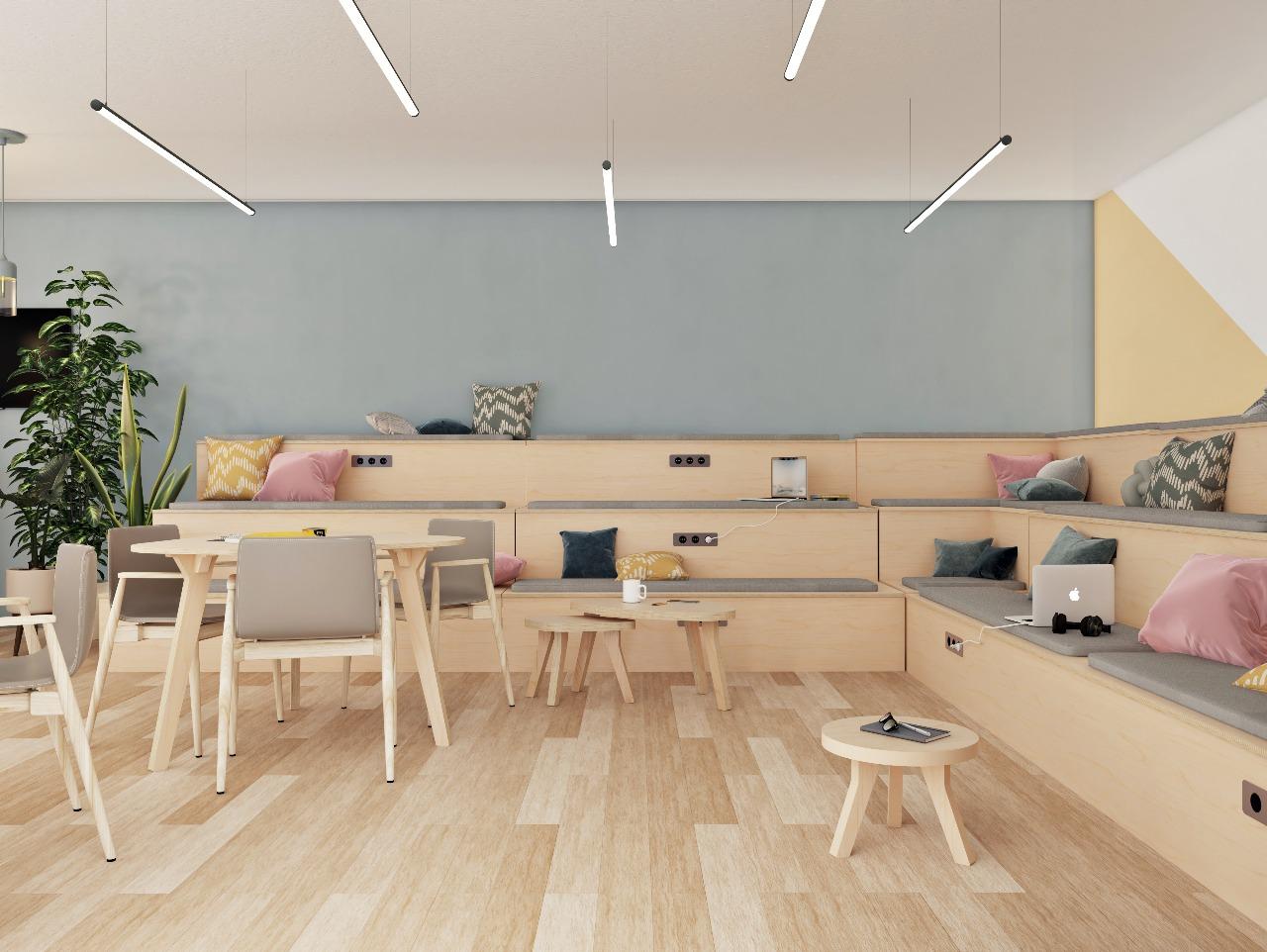 Espace de travail informel au style scandinave avec table et estrade en bois, ordinateurs branchés et coussins sur les assises