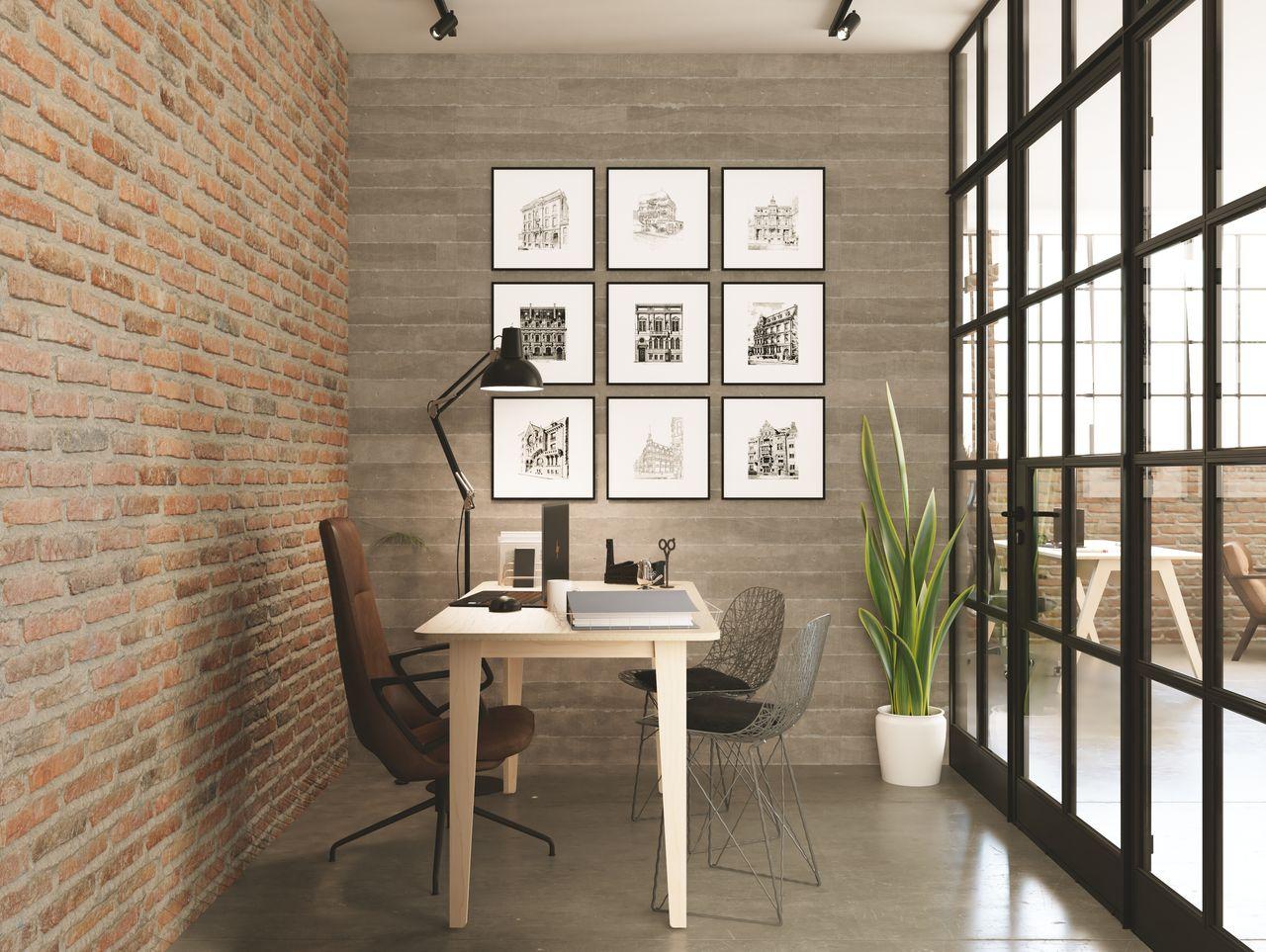 Bureau épuré design fabriqué en bois pour 1 personne disposé dans un espace de travail au style industriel avec une assise en cuir, des tableaux rétro, une verrière aux contours noirs, des briques rouges et une lampe noire