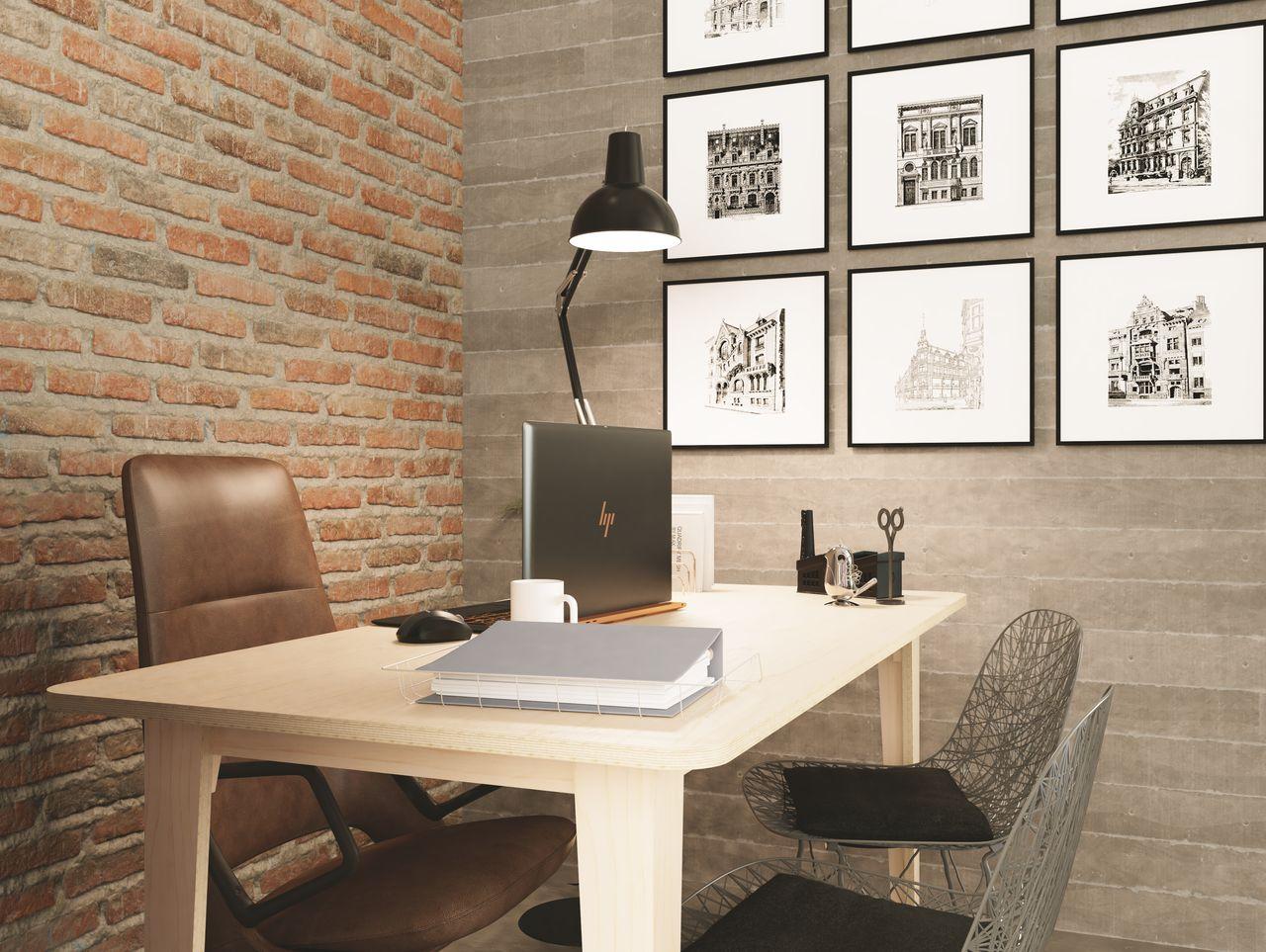 Bureau épuré au design simple et élégant disposé dans un bureau individuel à l'ambiance et au style industriel avec une lampe rétro noire et des briques rouges