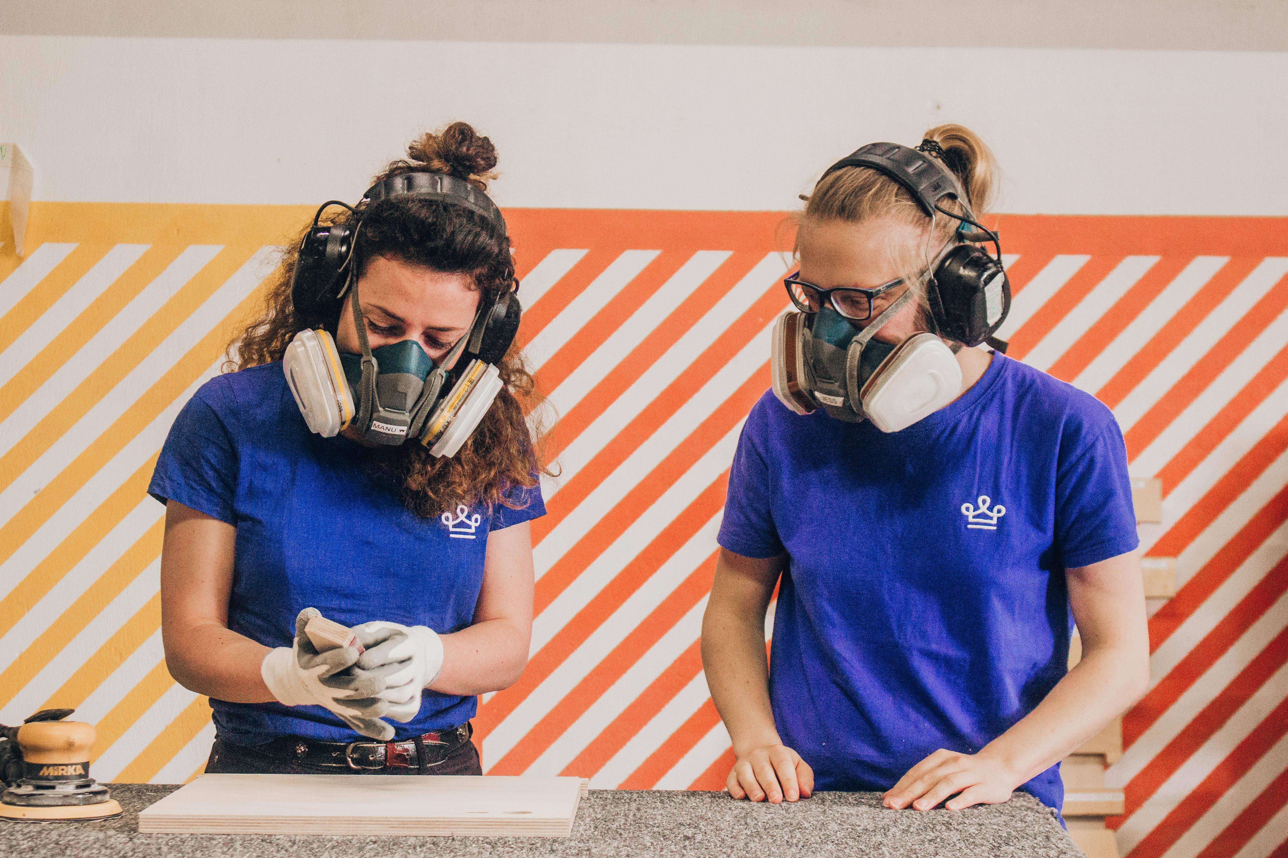 Deux femmes ébénistes dans un atelier de fabricant de mobilier de bureau qui font un onboarding