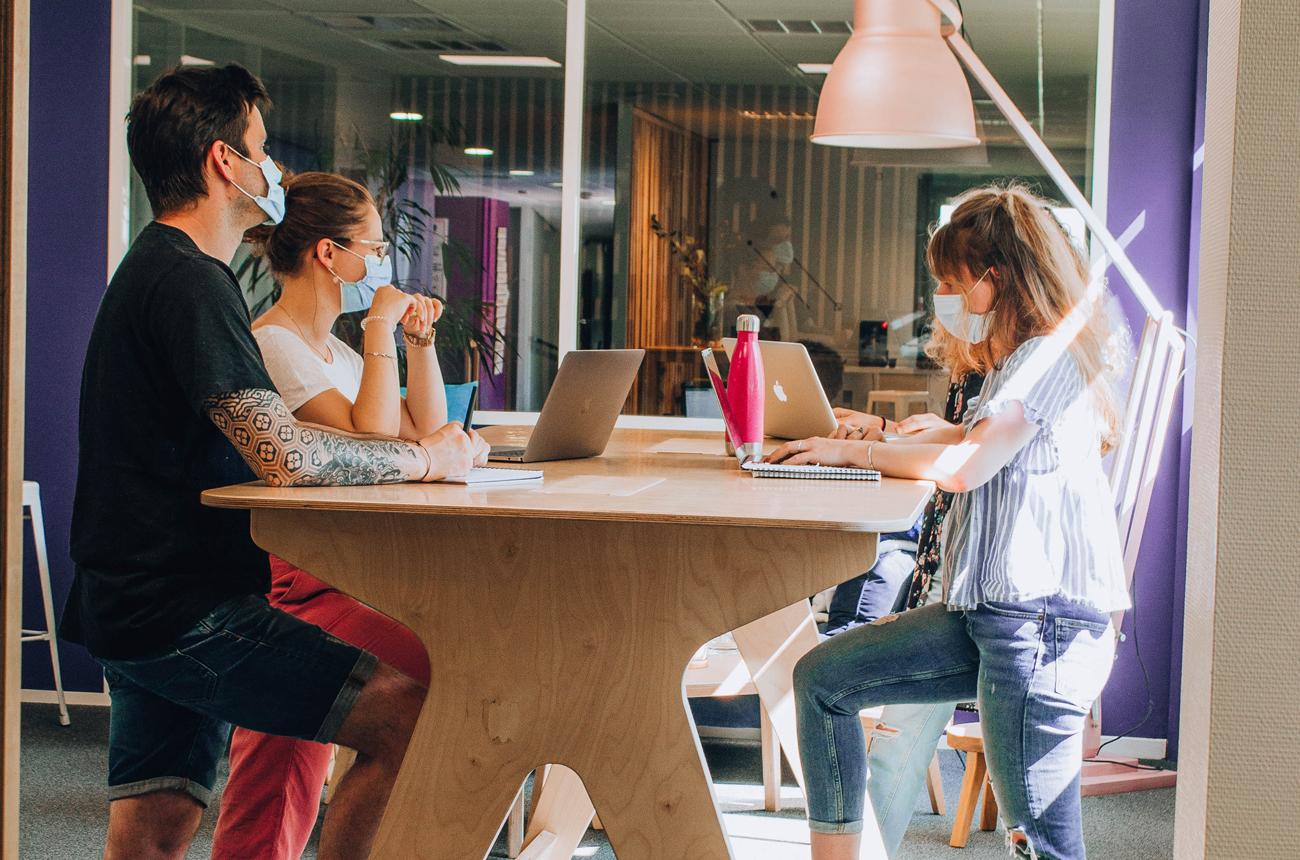 Des personnes debout en réunion de travail autour d'une table haute en b