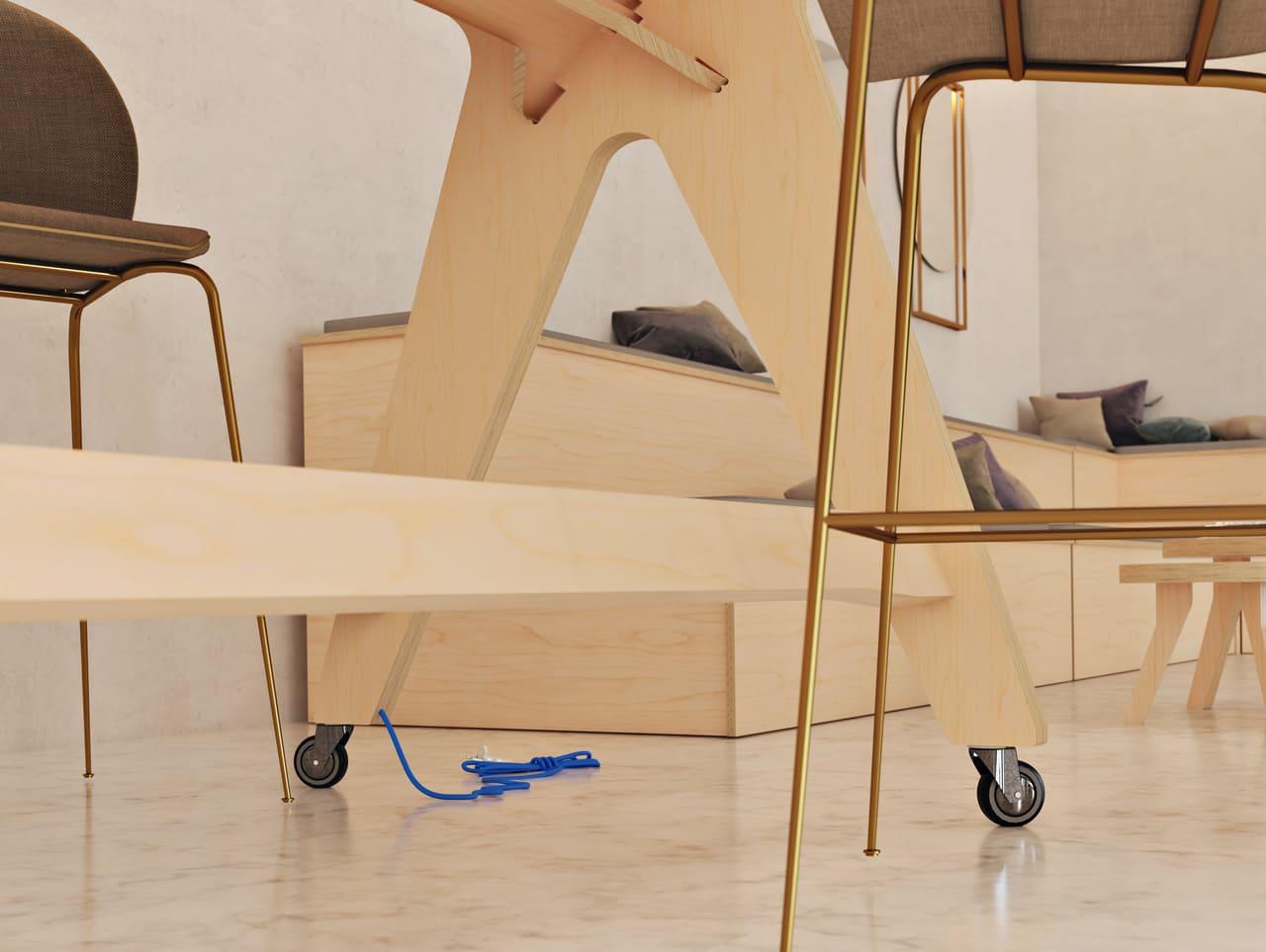 Table de réunion haute sur roulettes avec un cable bleu d'electrification sortant du pied et située dans une salle de réunion informelle à l'ambiance et au style contemporain avec des estrades en bois et des miroirs et chaises dorés