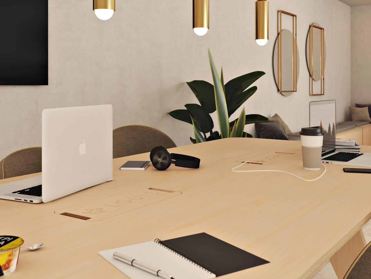 Table de réunion connectée avec trappes gravées au logo de l'entreprise et le câble électrique qui passe dans la goulotte pour brancher l'ordinateur. Une salle de réunion avec des plantes, des luminaires et miroirs au style contemporain.