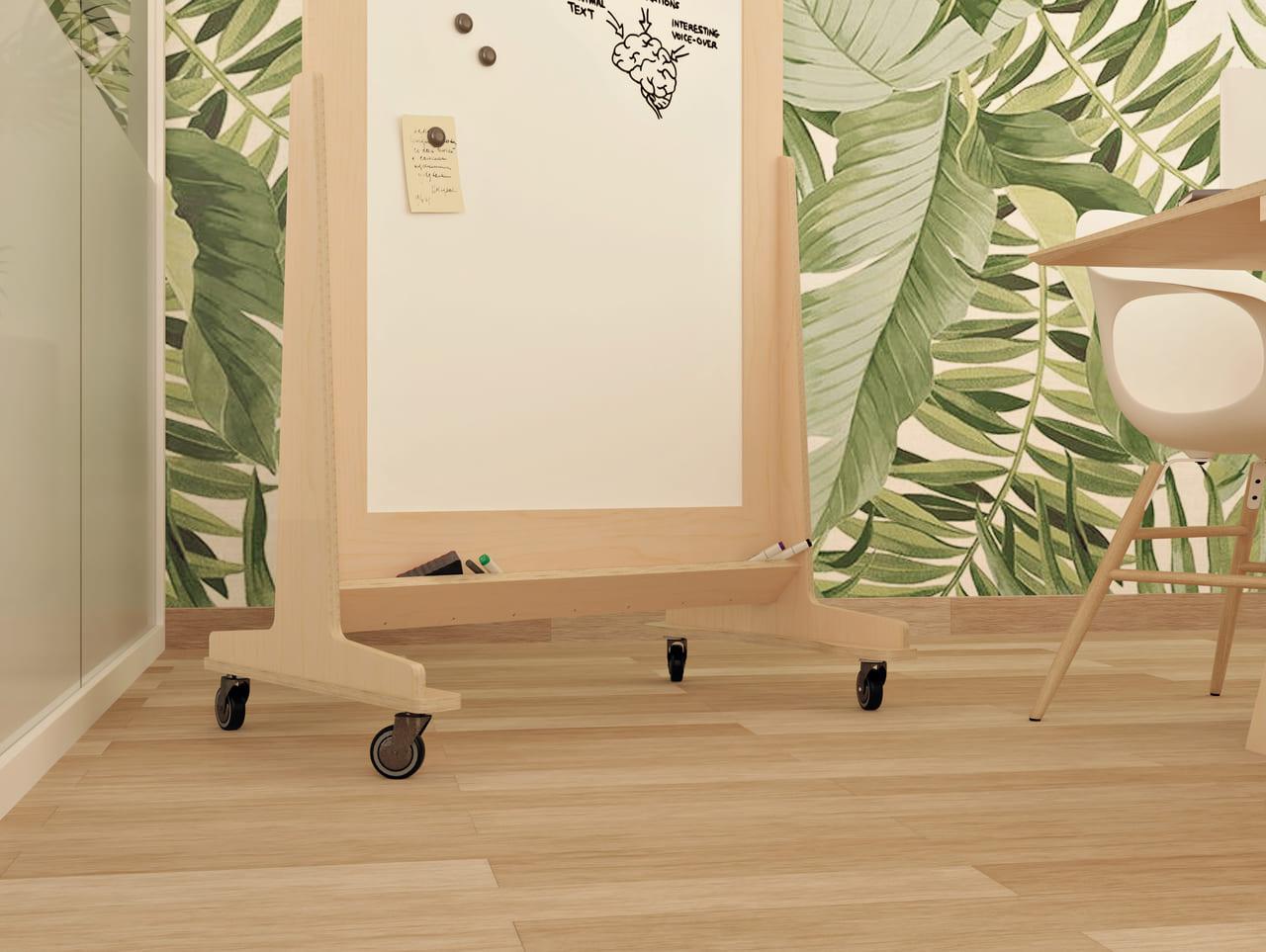 Tableau blanc sur roulettes avec cadre en bois et effaçable dans une salle de réunion au style scandinave avec un mur de papier peint motif feuilles d'arbre, une table de réunion et une paroi séparatrice en verre