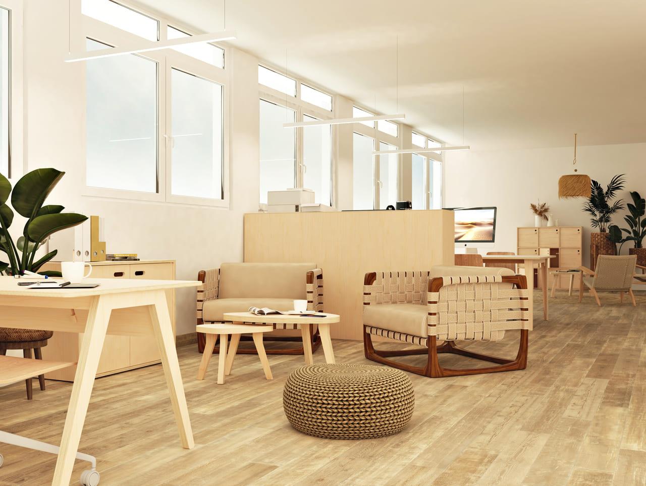 table basse gigogne bois en forme de galet placée devant un fauteuil tressé en bois, dans une salle de pause informelle à l'ambiance bohème ethnique végétale et moderne