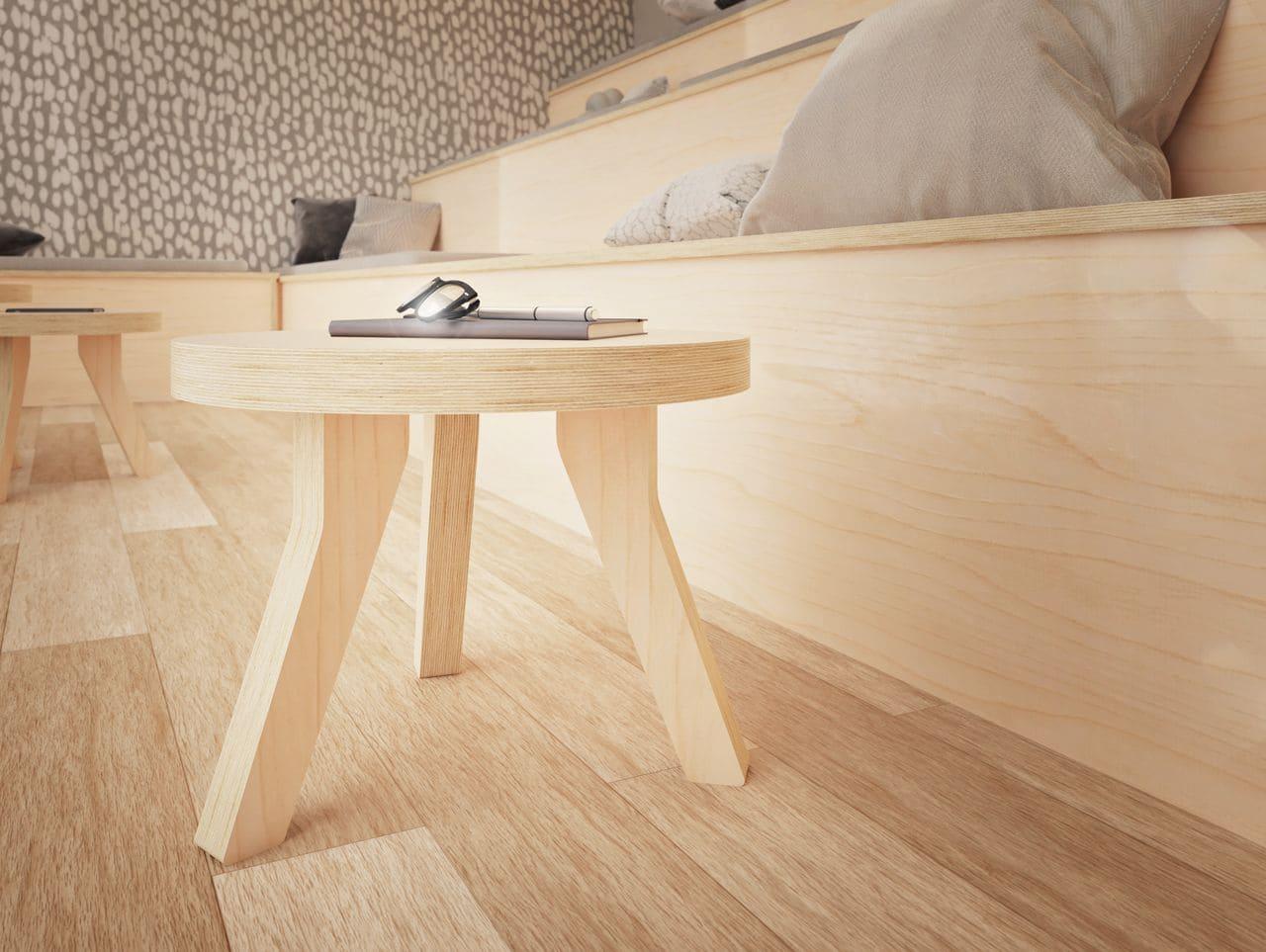table basse ronde placée devant une assise en bois avec des coussins colorés pour un espace détente au sein de l'entreprise où l'équipe peut venir lire ou se reposer dans une ambiance au style scandinave
