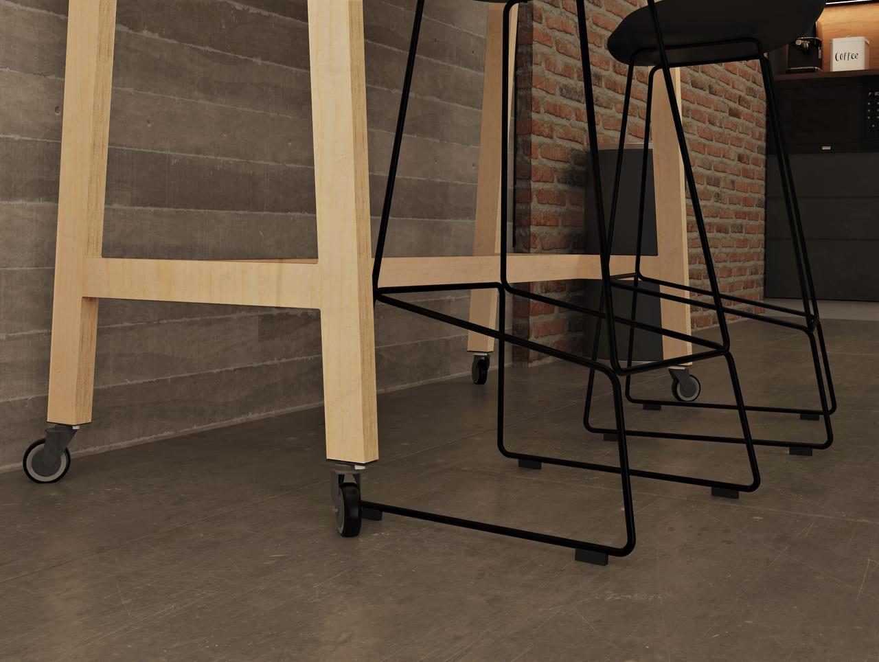 Mange debout avec des roulettes facilement modulable placée dans une salle de pause déjeuner au style industriel avec des briques rouges et du métal noir