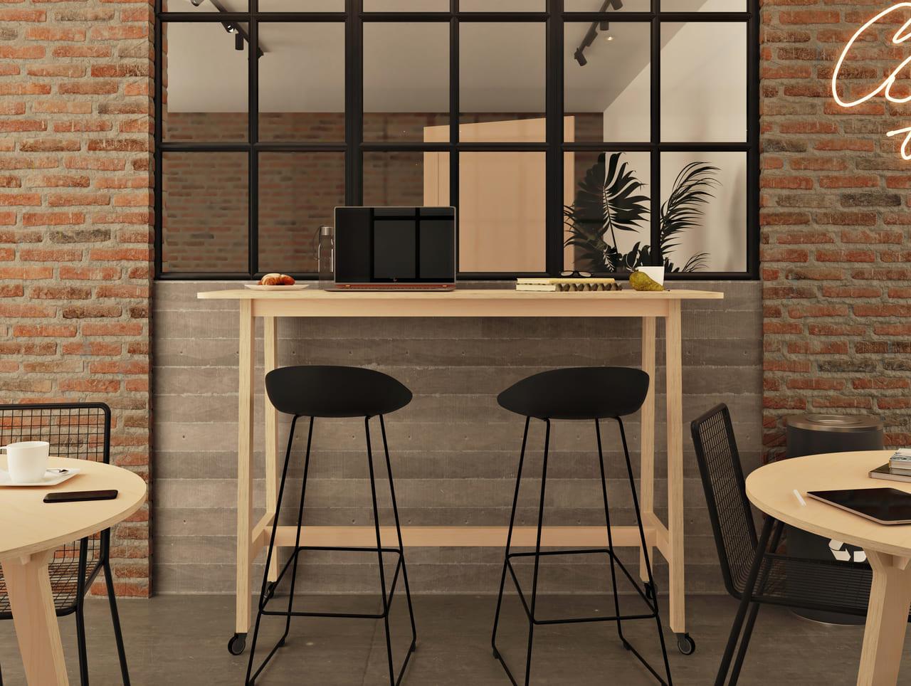 Mange debout en bois clair dans une salle de pause au style industriel avec une verrière aux contours noirs, des briques et des plantes vertes