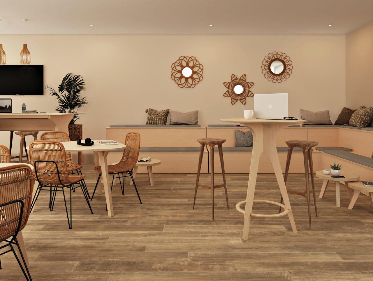 mange debout scandinave pour retrouver son équipe autour d'un café ou durant la pause déjeuner, placé dans une salle de pause au style et ambiance bohème et ethnique avec des meubles en bois, des miroirs de couleur dorée et des plantes vertes