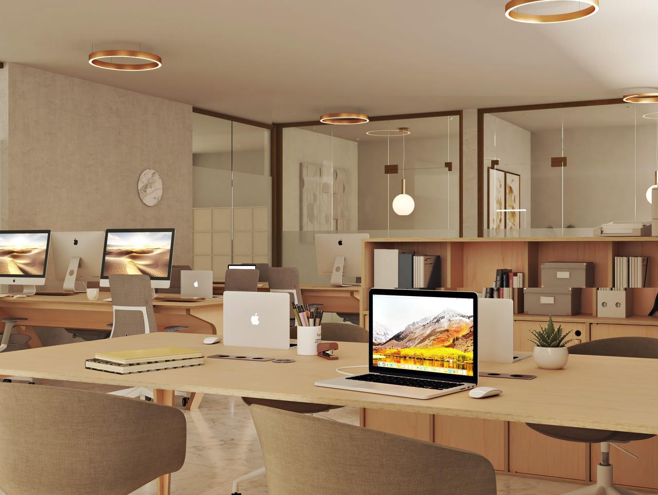 Bureau simple et moderne dans open space au style contemporain avec prises électriques sur le plateau, ordinateurs portables et petite plante
