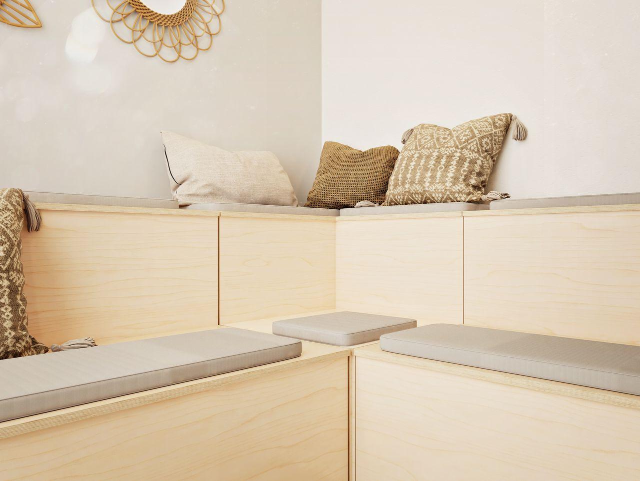 Banquette en bois sur deux niveau en angle avec coussins et galettes sur les assises
