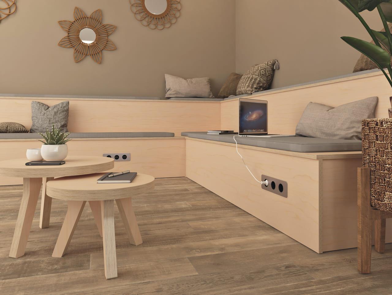 Estrade en bois avec des coussins et des prises intégrées pour brancher les ordinateurs et disposée dans un espace détente à l'ambiance bohème et ethnique décorée de miroirs de couleur dorée et de plantes vertes