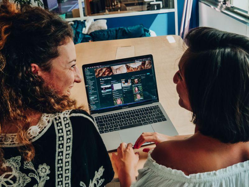 Deux jeunes femmes discutent et rient devant un ordinateur  posé sur un bureau lors d'un onboarding chez LOUIS