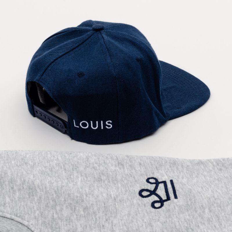 Une casquette bleu et un pull gris avec le logo LOUIS et une couronne brodée dessus
