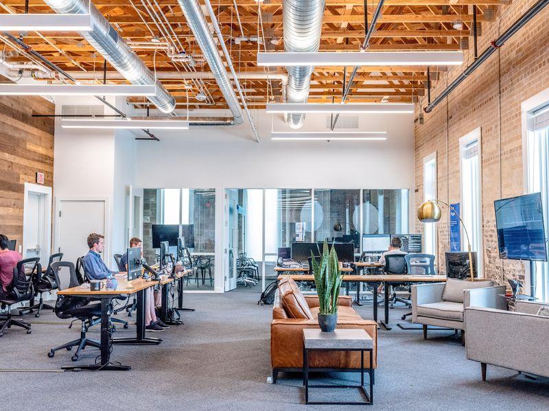 Grand open space style industriel avec des gens qui travaillent espacés sur des bureaux en bois et métal placés devant des canapés, tables d'appoint avec plantes et fauteuils.