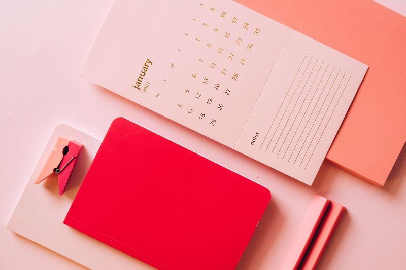 Un calendrier blanc de janvier 2021 posé sur un fond rose à côté d'un carnet rouge et d'une pince à linge rose