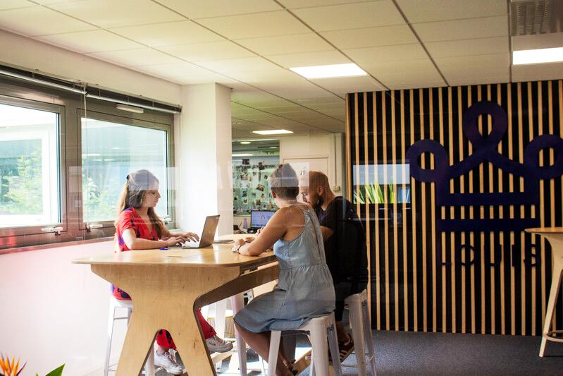 3 personnes assises autour d'une table de réunion haute pour nommer un responsable déménagement dans un bureau décoré avec une couronne LOUIS bleu sur le mur du fond