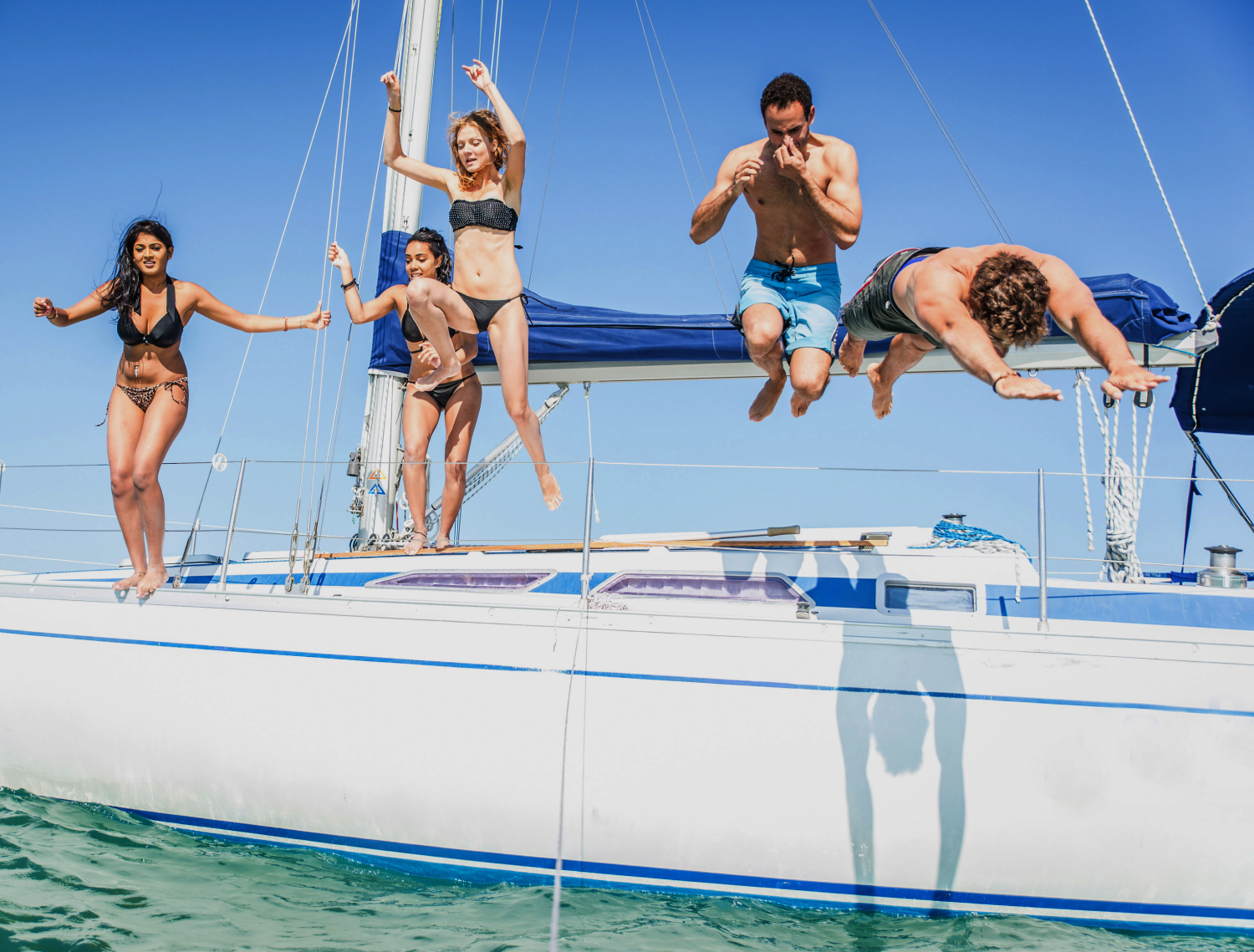friends on a boat jumping into the sea