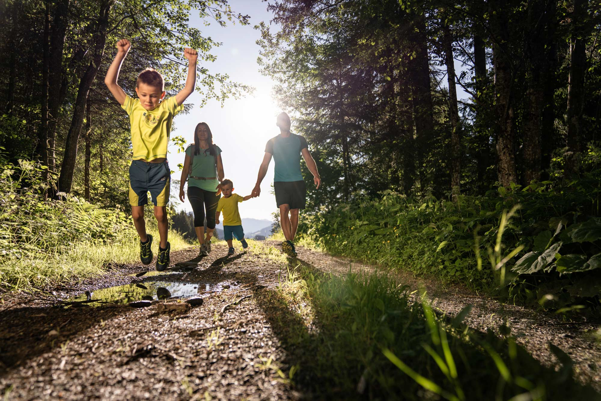 Eine Familie beim Wandern. Ein Junge springt über eine Pfütze.