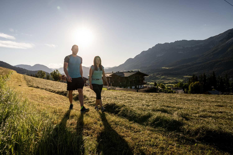Urlauberpaar wandert durch die frisch gemähte Wiese etwas oberhalb des Naschberghofes.
