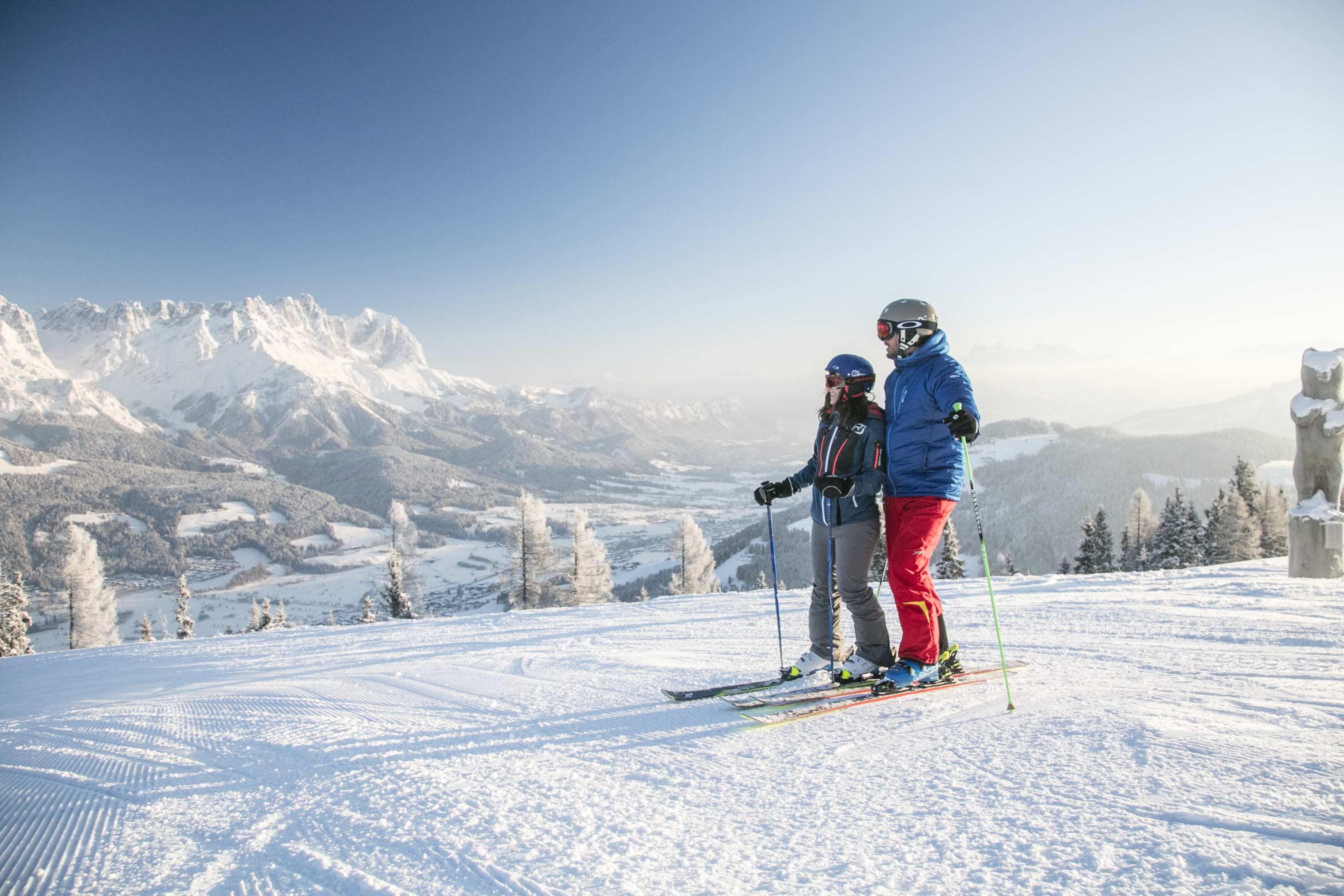 Ein Skifahrer-Pärchen auf den Pisten der Skiwelt genießt den Blick auf den Wilden Kaiser.