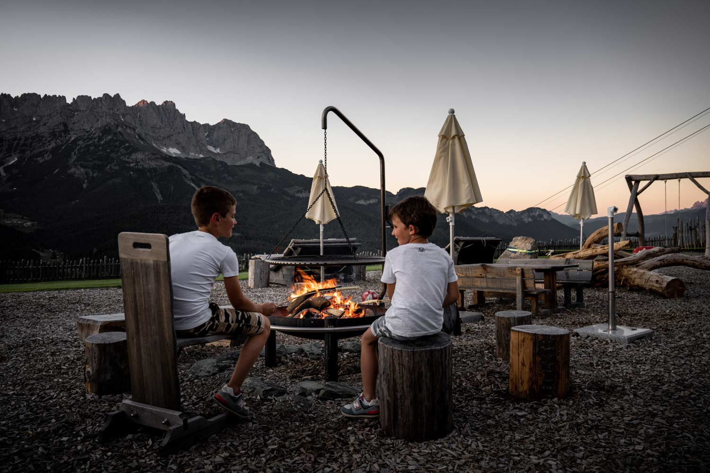 Kinder backen Steckerlbrot an der Feuerstelle
