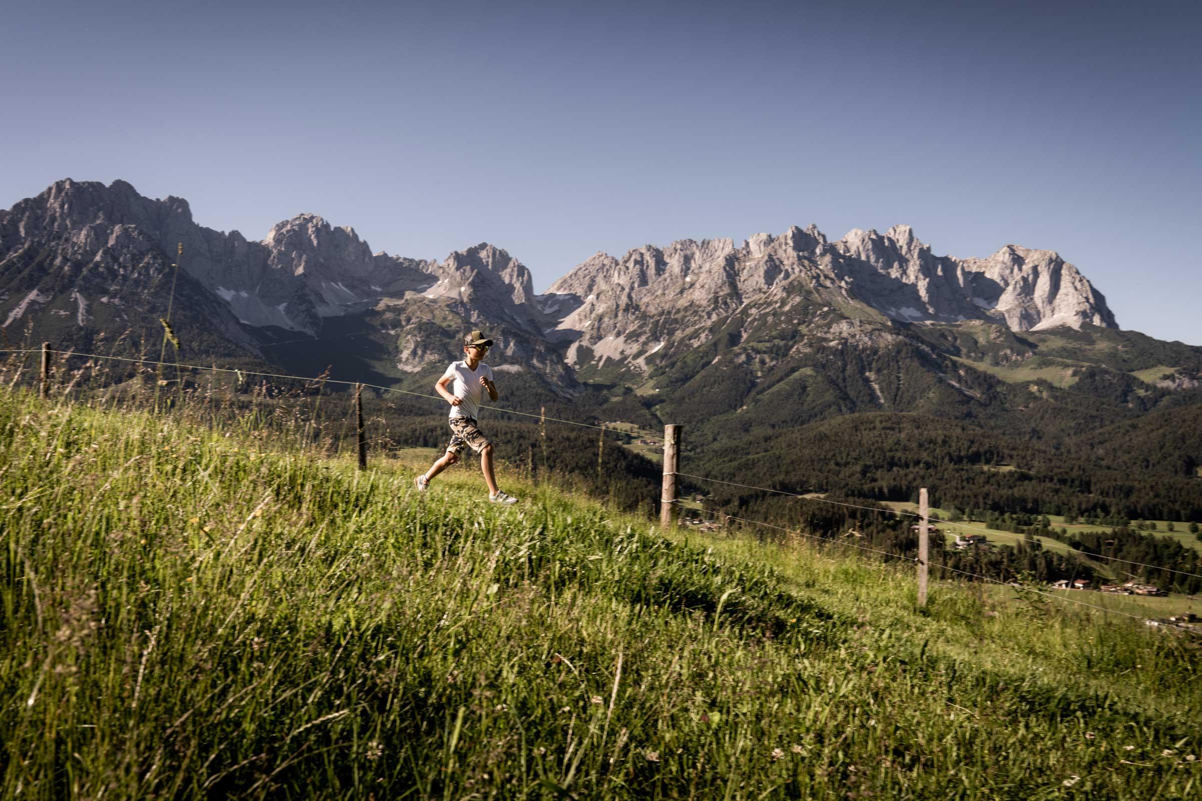 Ein junge läuft durch die Blumenwiese. Im Hintergrund thront der Wilde Kaiser.