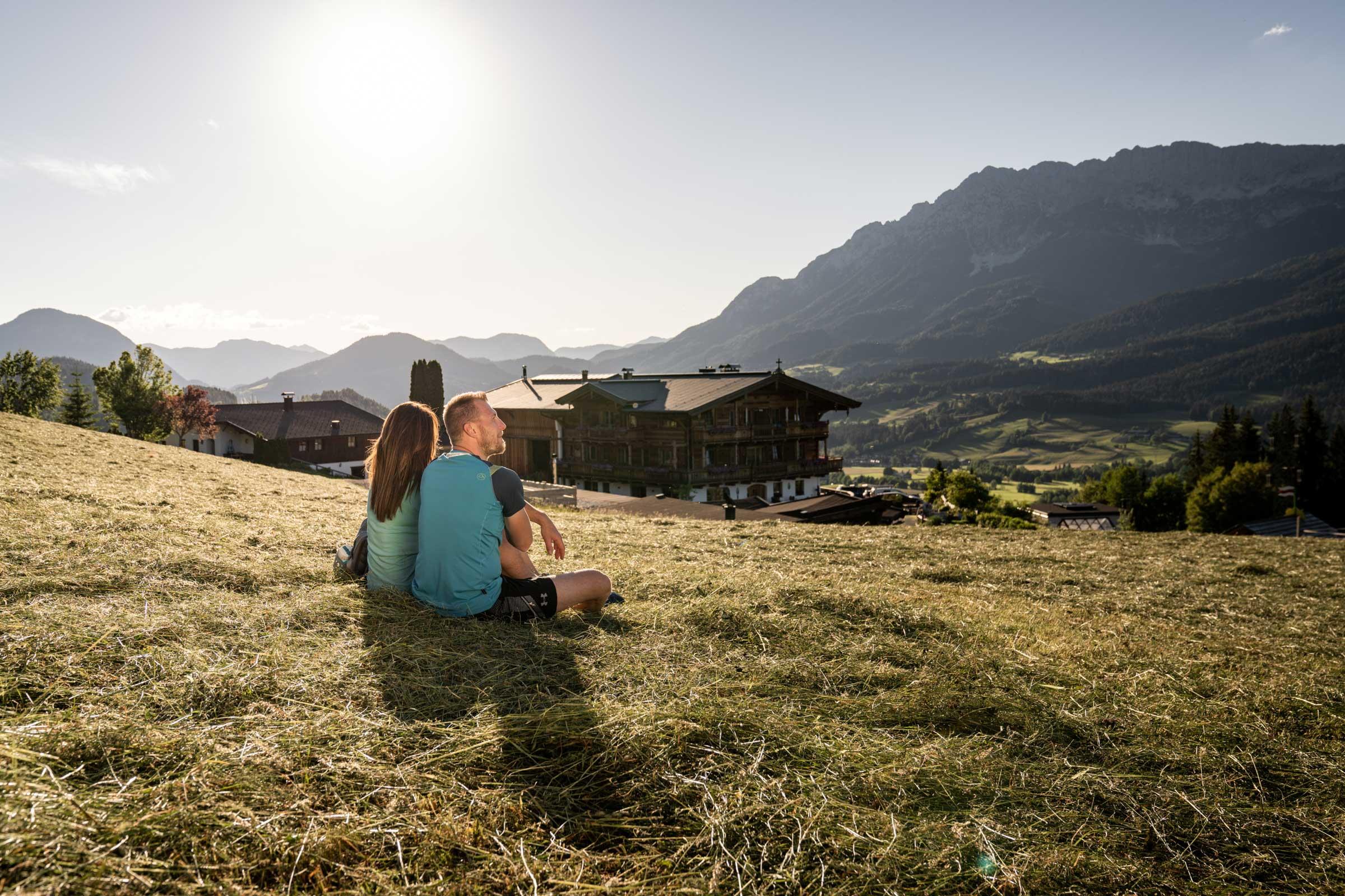 Urlauberpaar sitzt frisch gemähter Heuwiese etwas oberhalb des Naschberghofes und genießt den Ausblick auf den Wilden Kaisers.