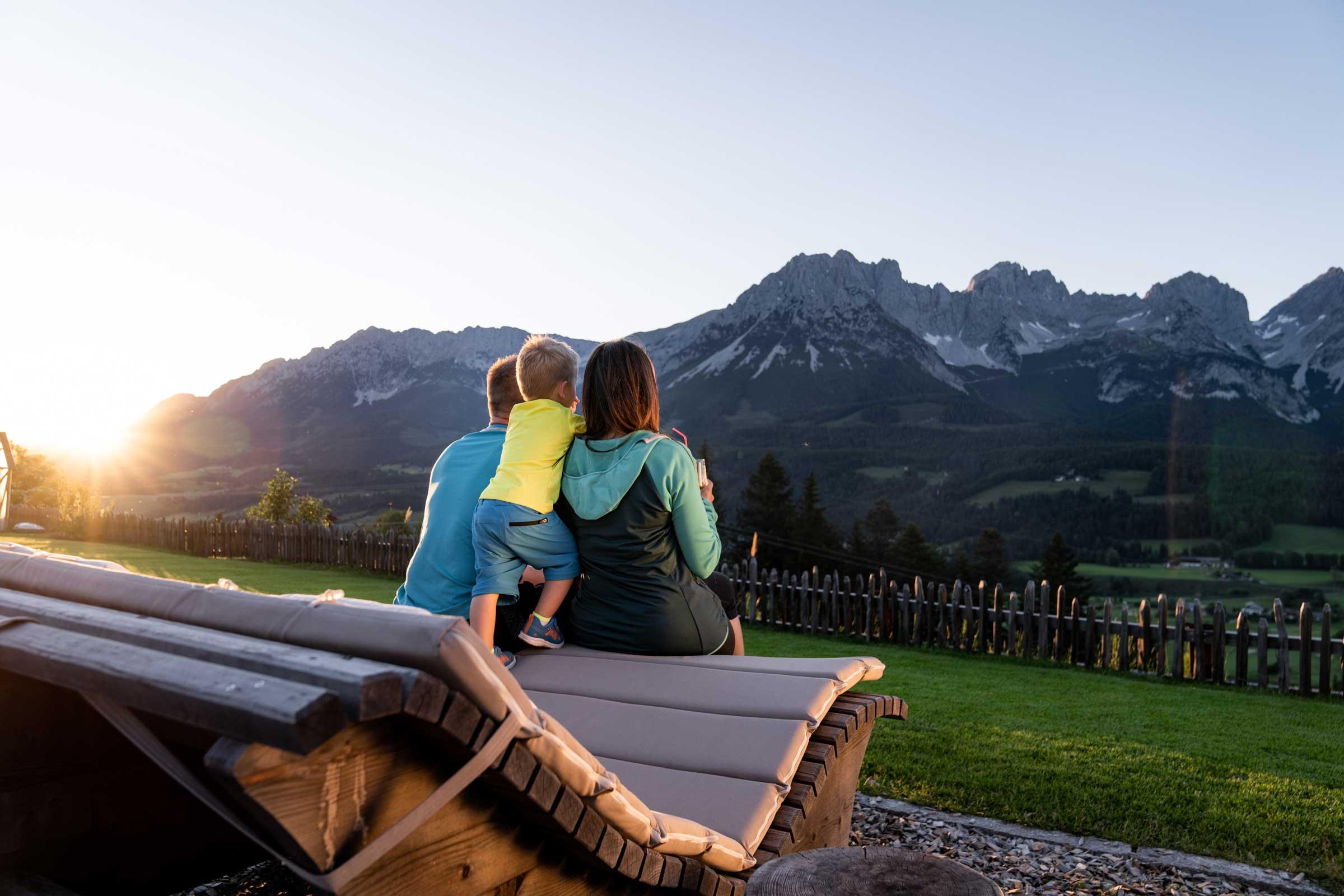 Urlauberfamilie sitzt auf gemütlicher Ruheliege im Garten des Naschberghofes und genießt das Bergpanorama des Wilden Kaisers bei untergehender Sonne.
