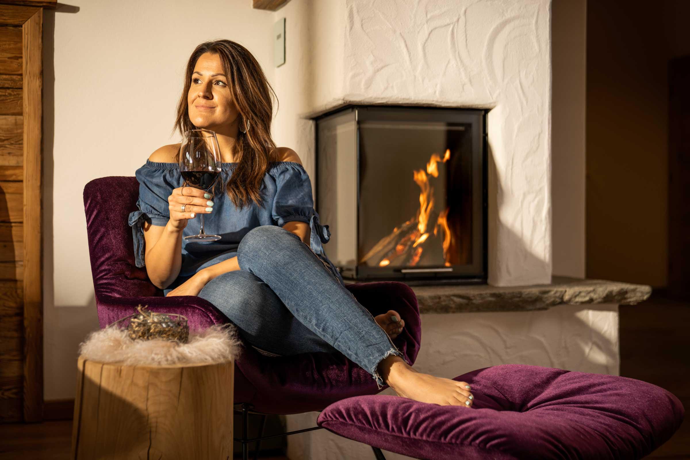 """Eine junge Urlauberin genießt ein Glas Rotwein vor dem wärmenden Kachelofen des Naschberghof Appartements """"Hartkaiser""""."""