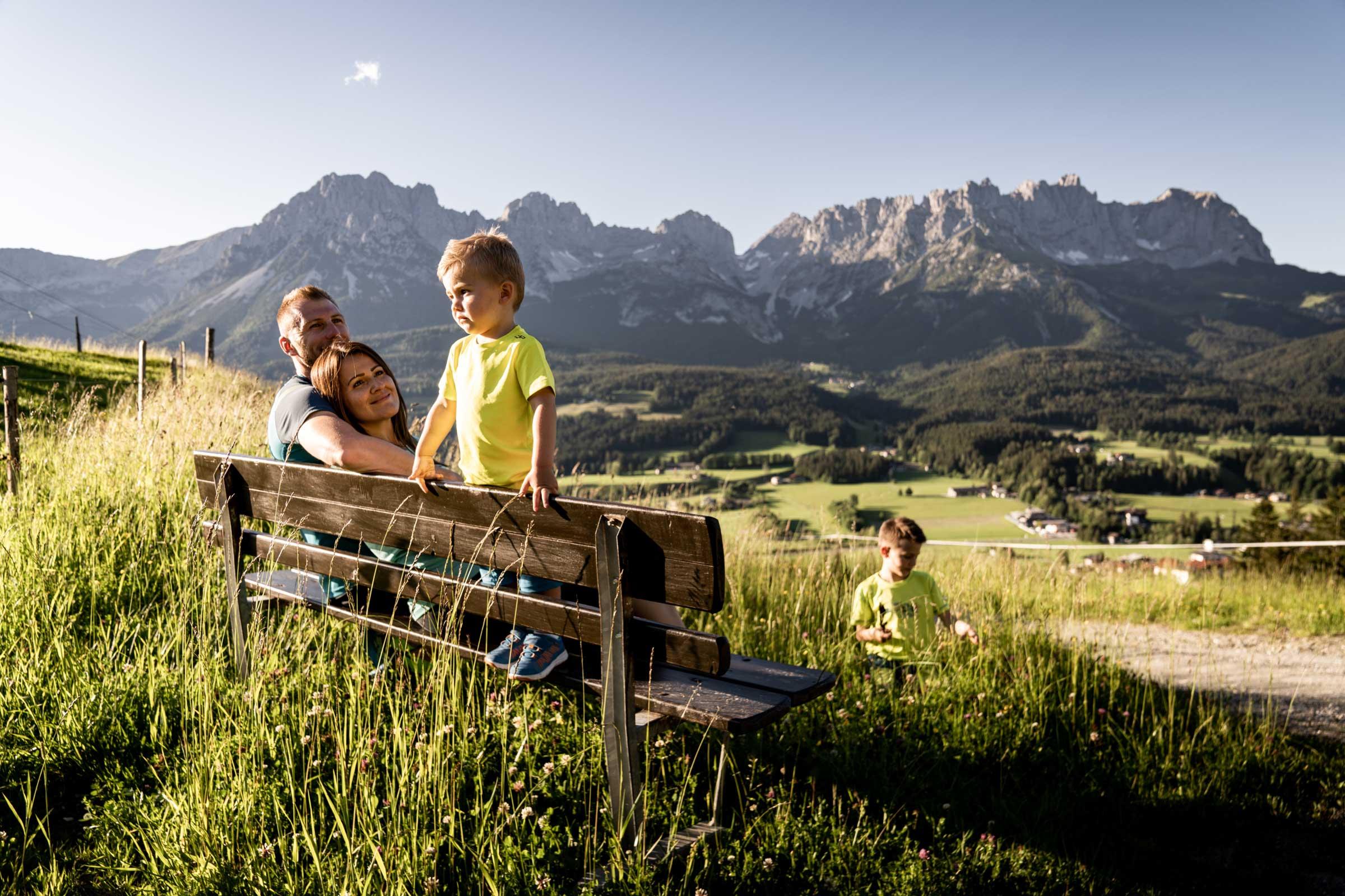 Eine Urlauberfamilie auf einem Rastplatz, wenige Schritte oberhalb des Naschberghofes mit Blick auf den Wilden Kaiser.