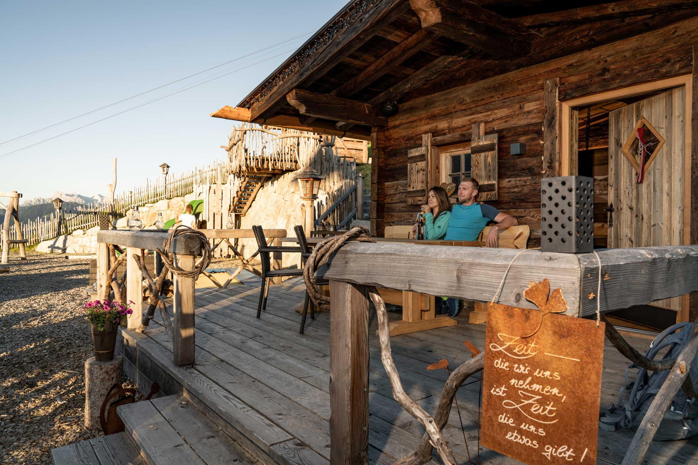 Ein Paar genießt seinen Urlaub auf der Terrasse der Grillhütte.