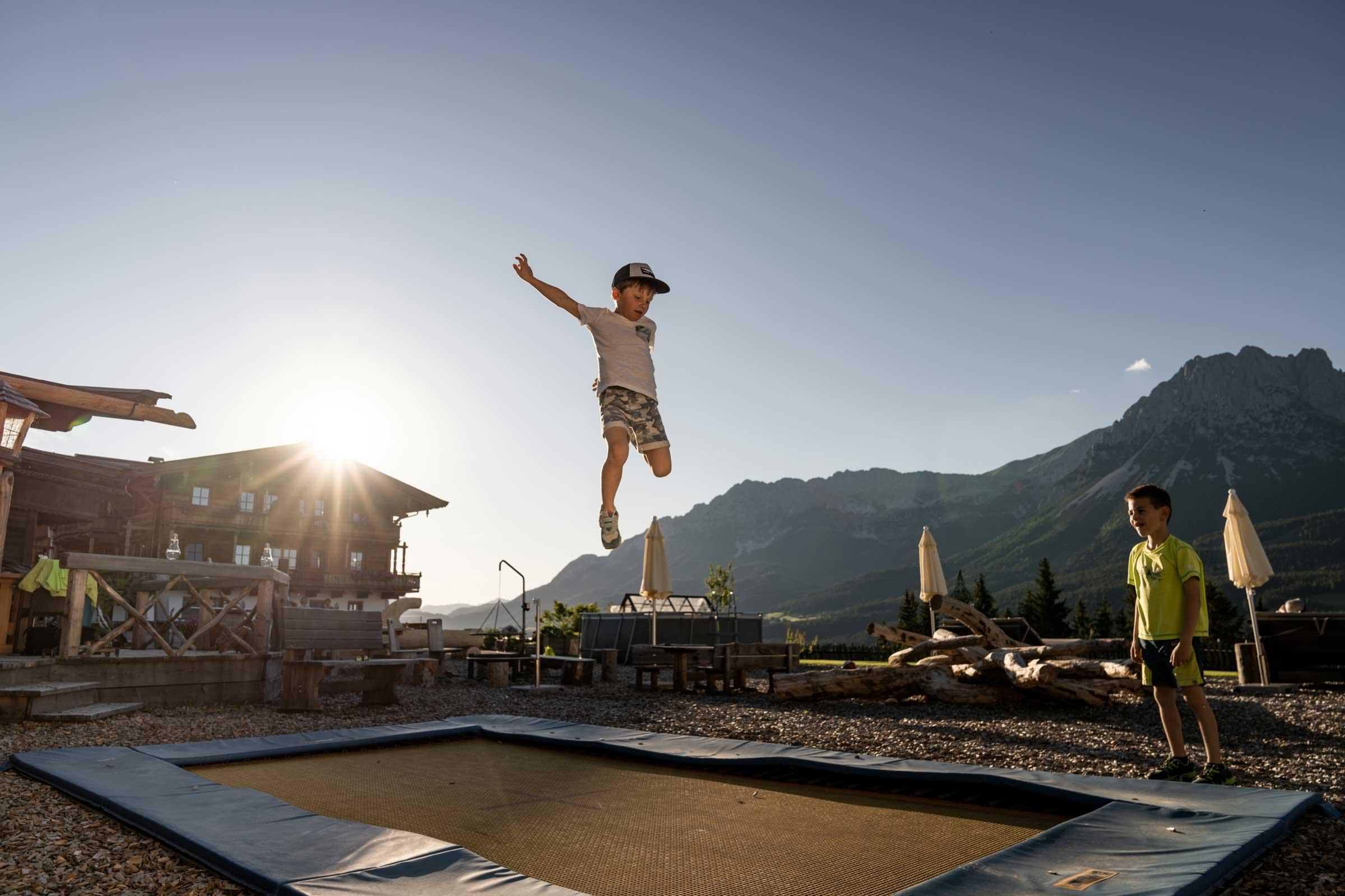 Ein Junge springt am Trampolin des Naschberghofes.