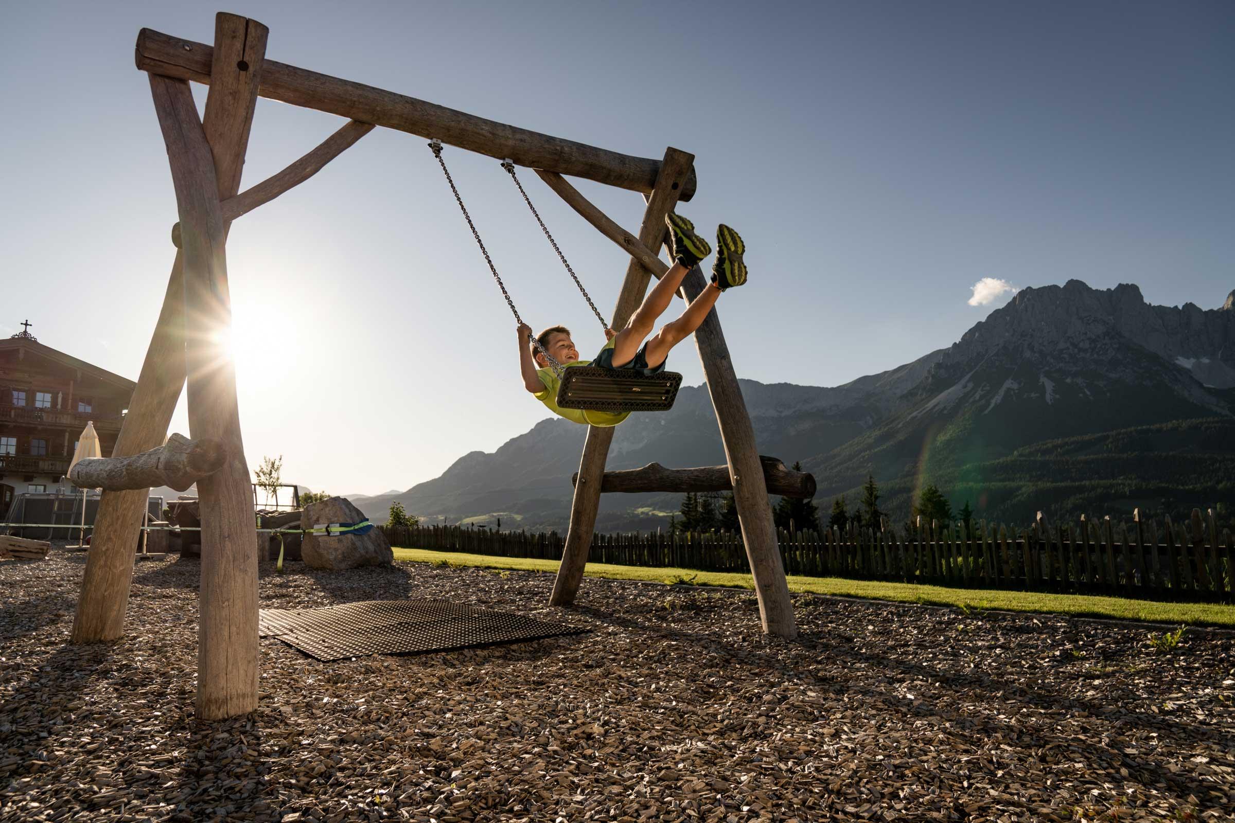 Ein Junge beim Schaukeln am Kinderspielplatz des Naschberghofes.