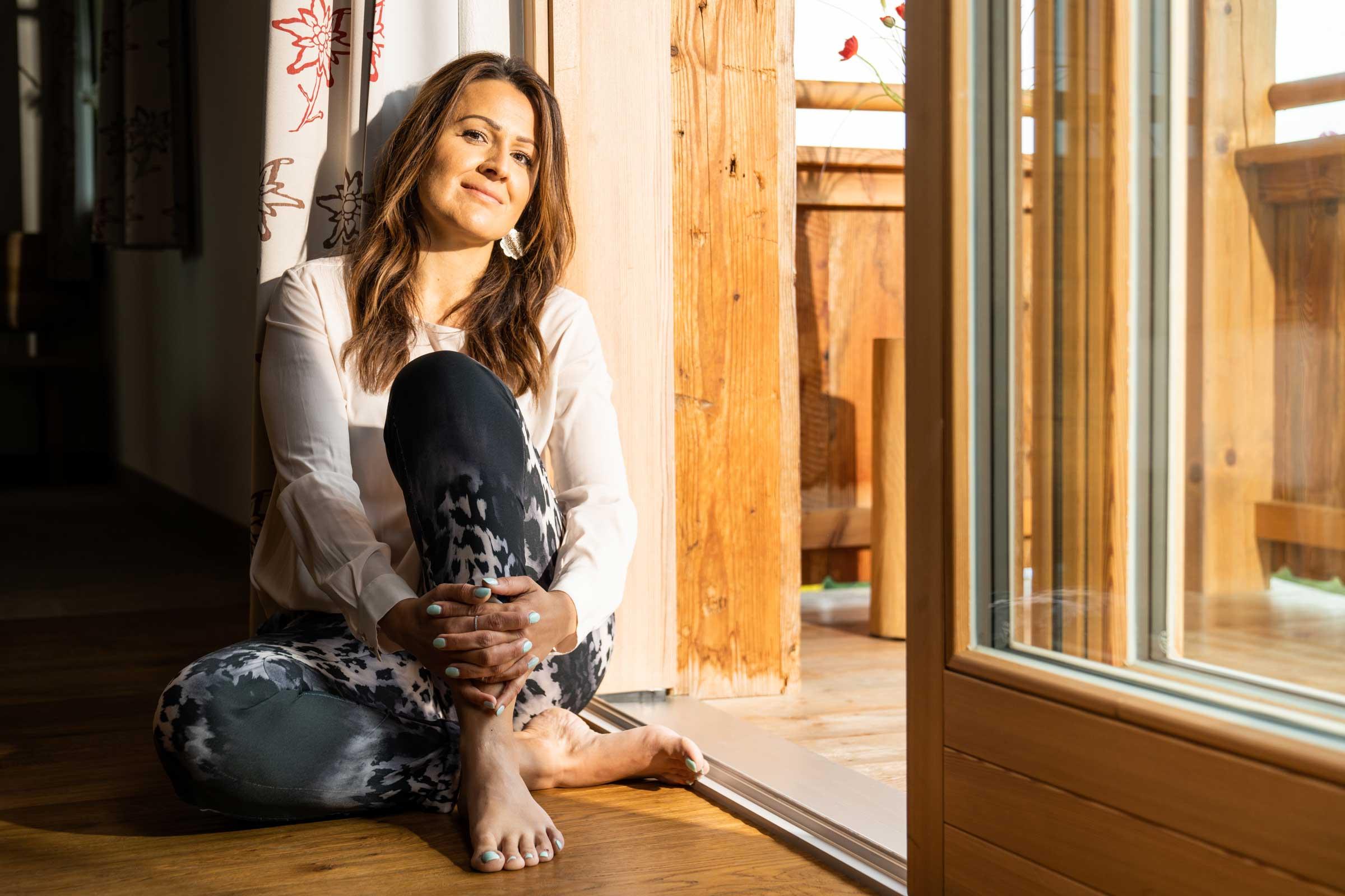 Urlauberin sitzt in der Terrassentürschwelle und genießt die Ruhe.
