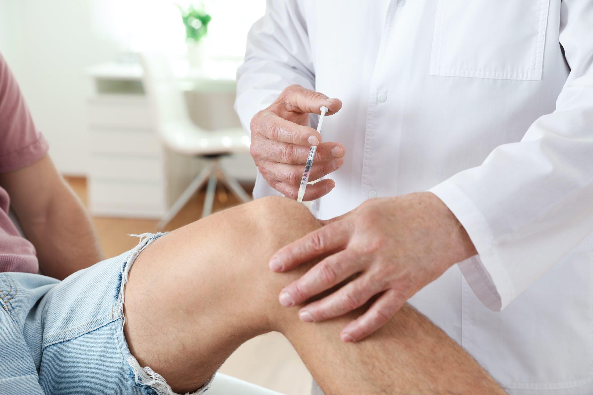 Arzt spritzt Hyaluronsäure in das Kniegelenk