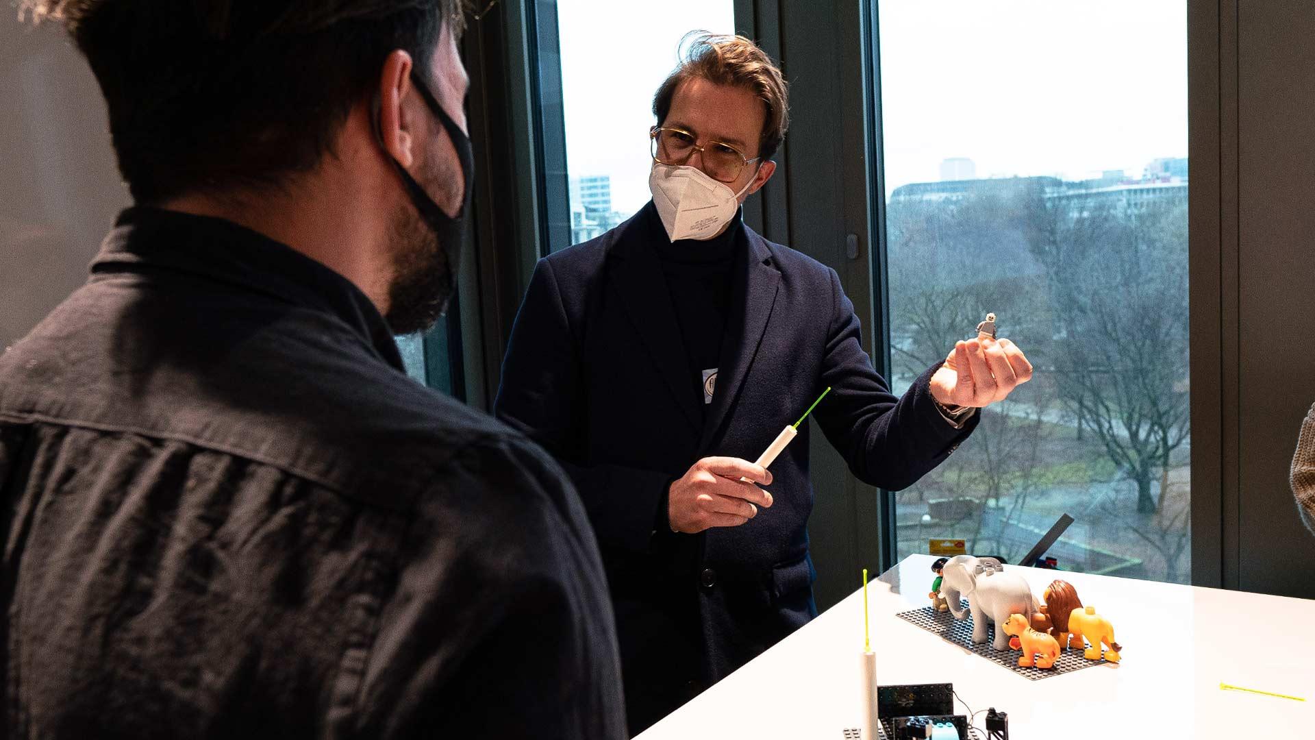 Man with mask explaining something with Lego