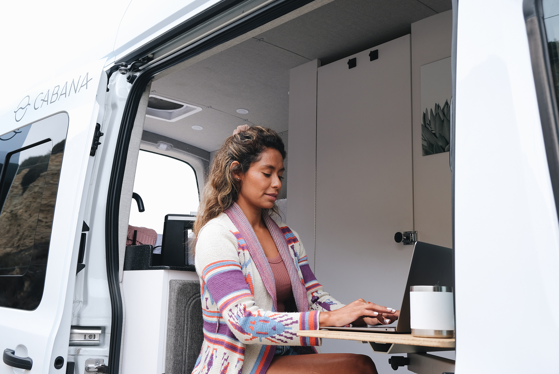 woman working at laptop inside van