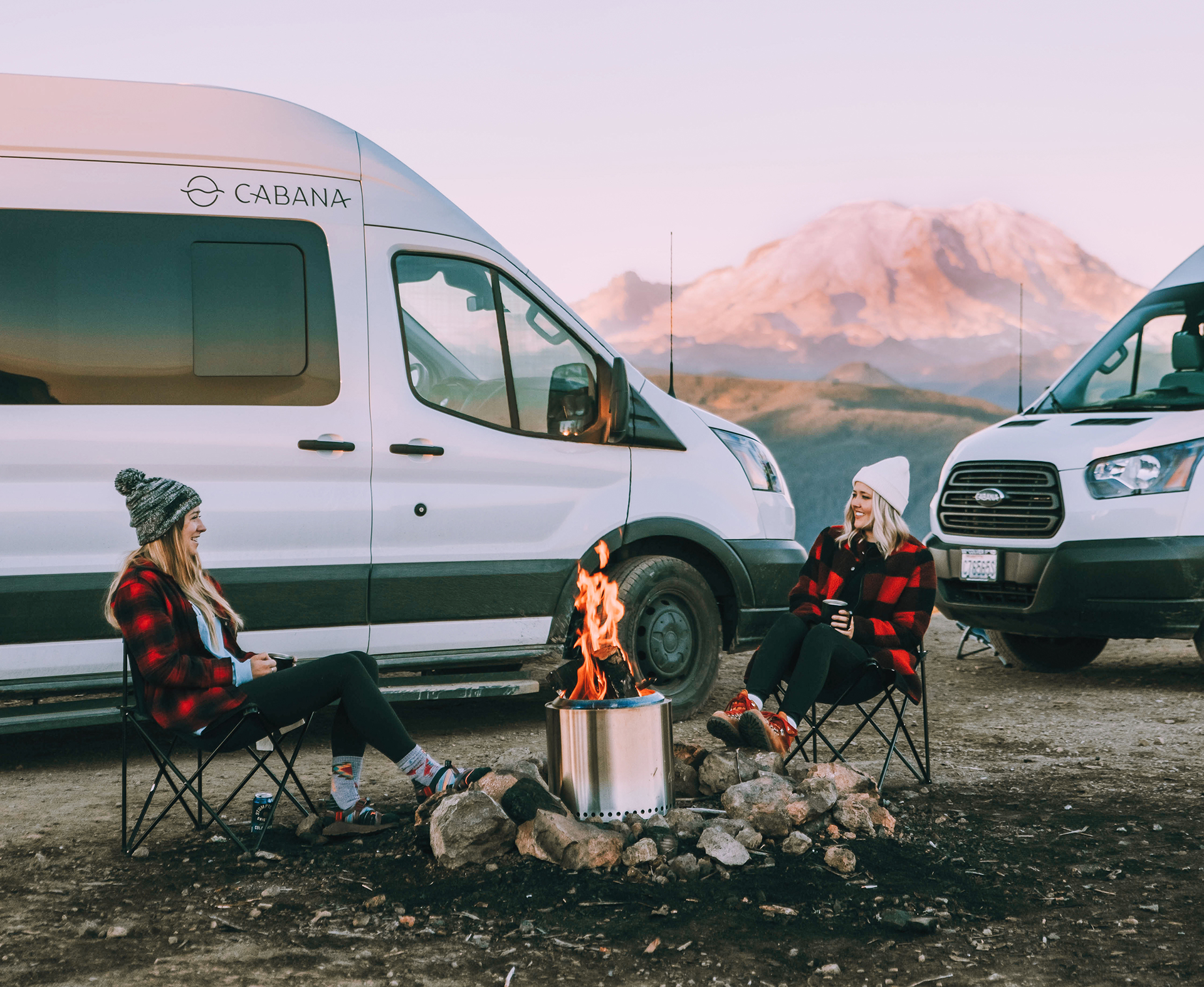 couple sitting around campfire, vans in the background