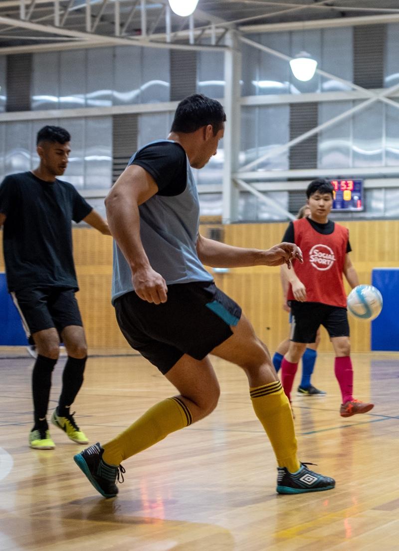 A male Futsal player kicks the ball upcourt