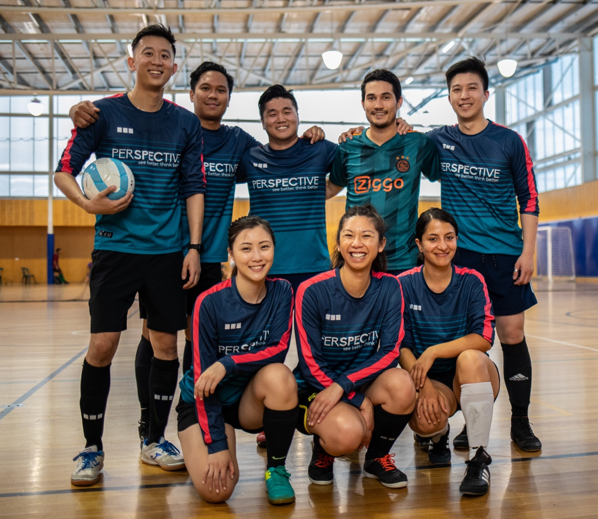 A mixed Futsal team stand for a photo