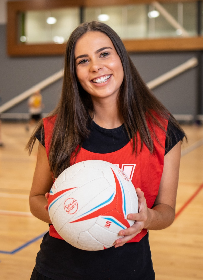 A female netball player smiles while holding the ball