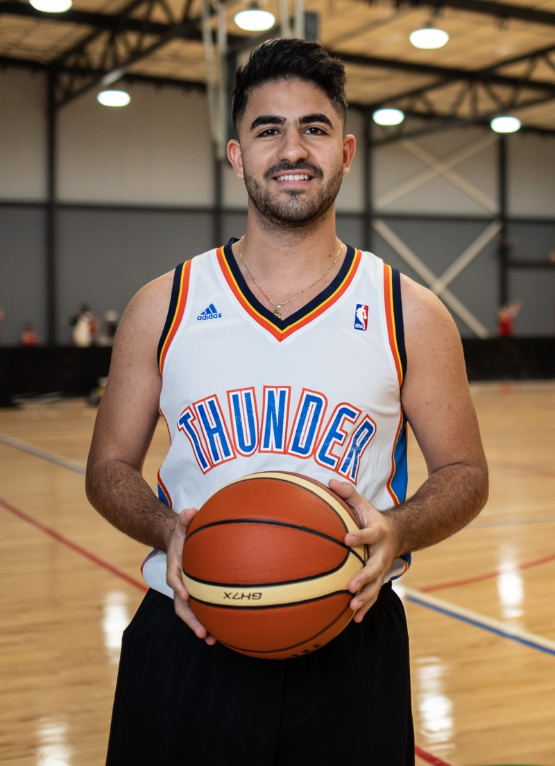 Male Basketball player stands with the ball