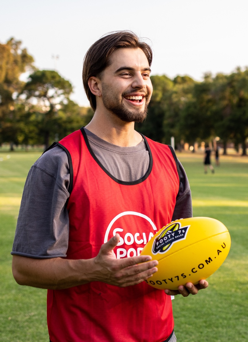 Male Footy 7s player stands with the ball