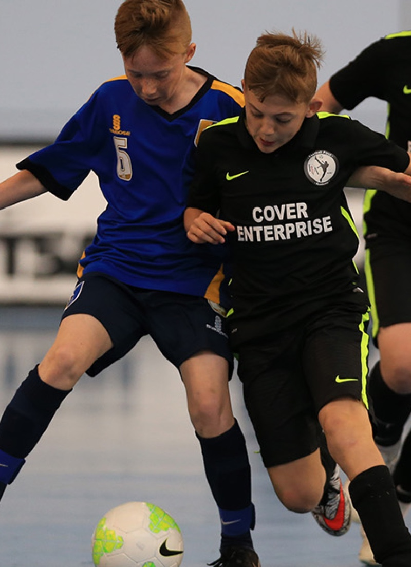 Two junior Futsal players jostle for the ball
