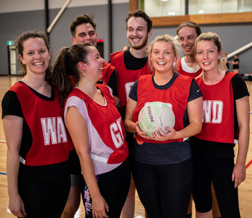A social Netball team laugh as they stand for a team photo