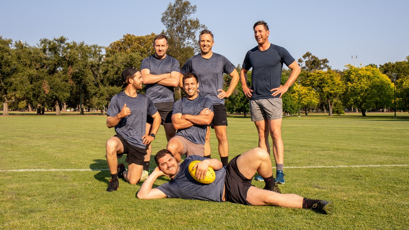 An all-male social Footy 7s team stand for a photo
