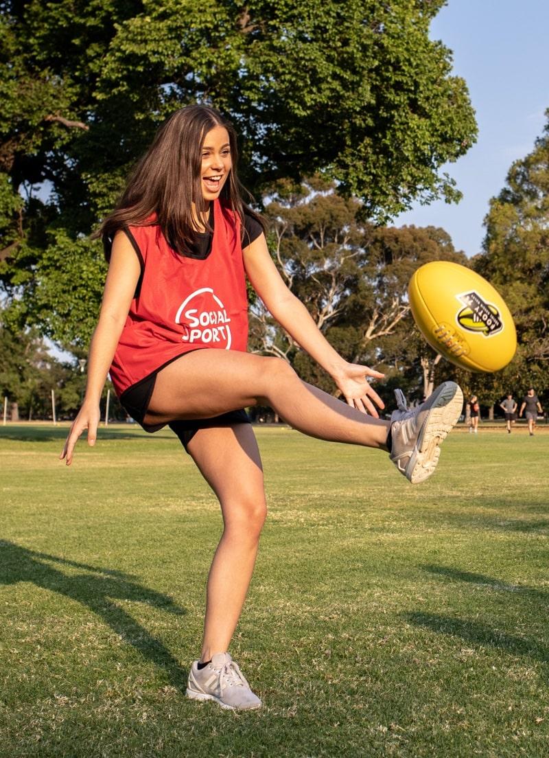 A female player kicks a footy