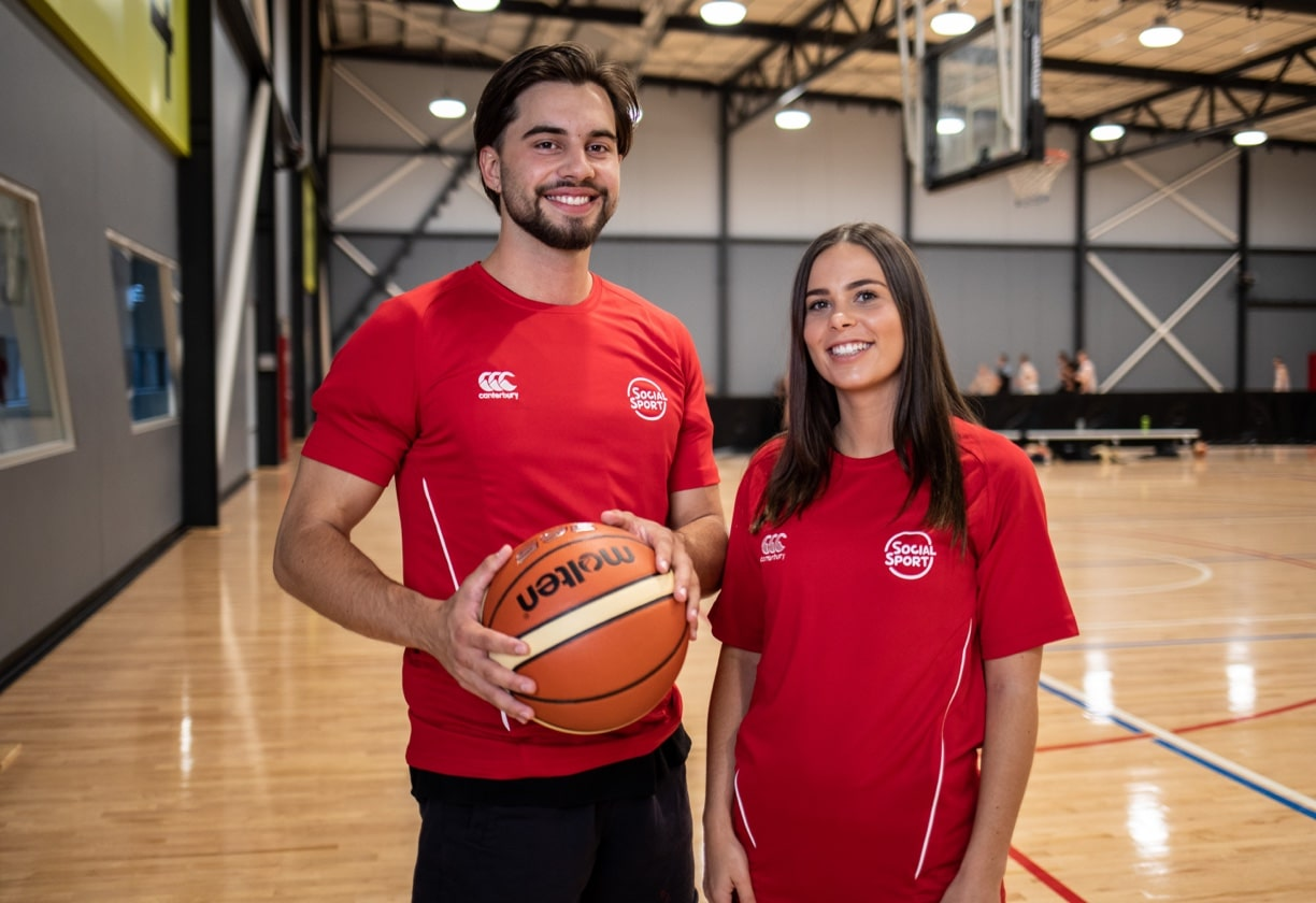 Two social Basketball players stand beside the court